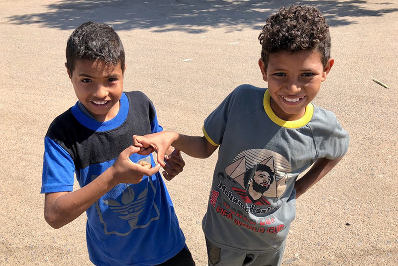 Two kids in Edfu make the shape of a heart with their fingers, Egypt