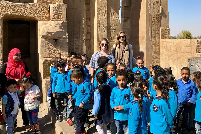 Schoolchildren gather for a photo with travelers at a temple in Egypt