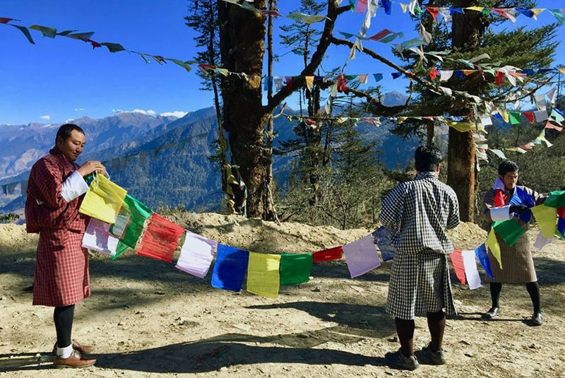 Hanging prayer flags on a mountain pass in Bhutan