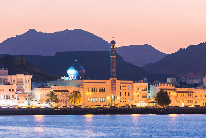 Muttrah Harbor and Old Town at dusk in Muscat, Oman
