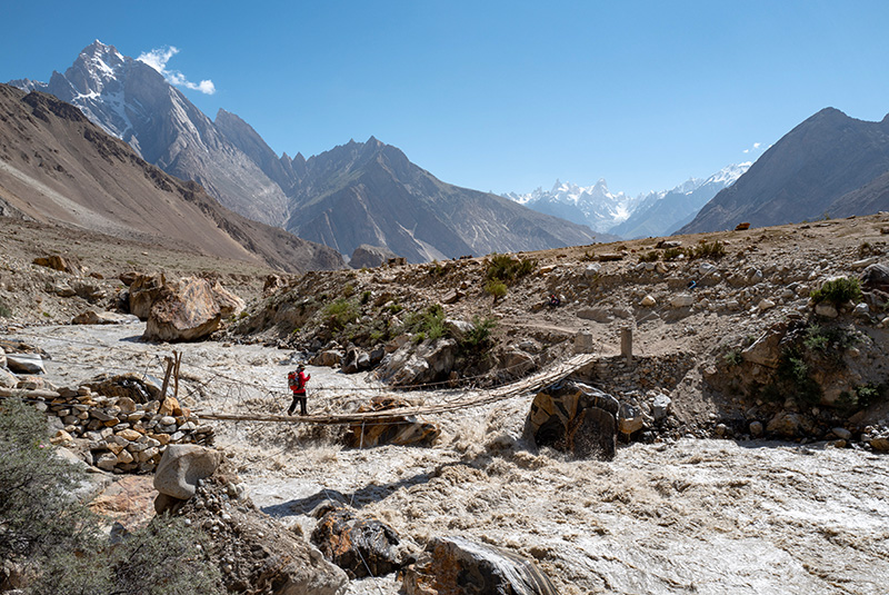 Trekker crossing a bridge en route to K2 and Broad Peak Base Camp, Pakistan