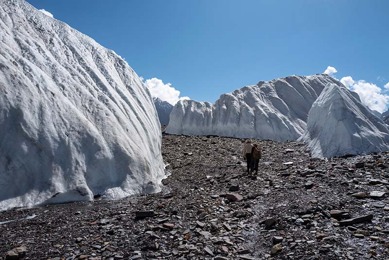 Trekkers hike through a glacier passage on the way to K2, Pakistan