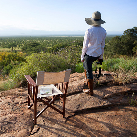 A woman on safari looks out over Meru National Park from a rock kopje in Kenya.