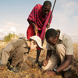 Boy with Maasai guides looking for baboon spiders in Kenya.