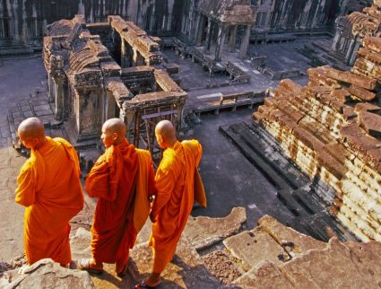 Three monks overlook Angkor Wat, Cambodia with GeoEx