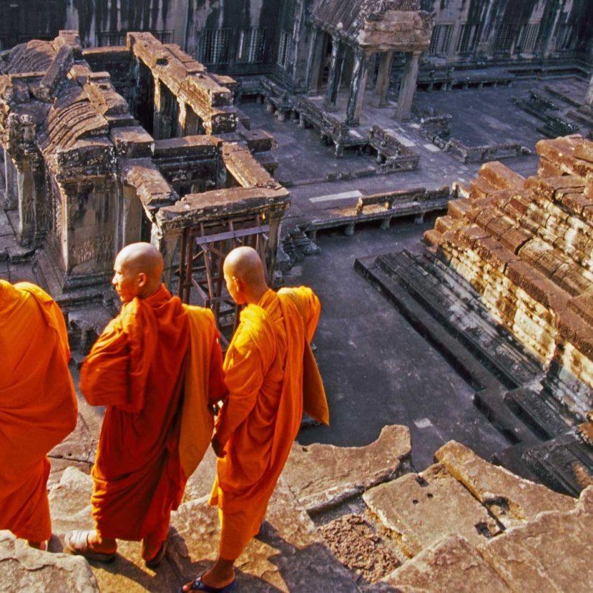 Three monks overlook Angkor Wat, Cambodia with GeoEx