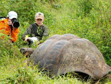 Mother and son photographing a Galapagos tortoise on Santa Cruz, Galapagos