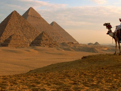 A man on a camel looks at the Giza Pyramids, Egypt