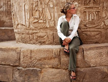 A woman sitting at the base of a massive stone column in Karnak, Egypt