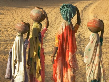 Girls wearing saris and holding water jugs in Rajasthan, India with GeoEx