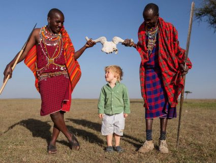Two Maasai play with a young guest in the Masai Mara, Kenya
