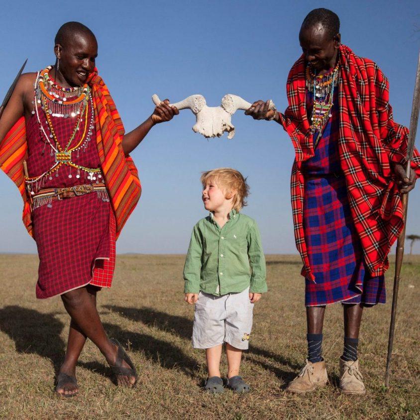 Two Maasai play with a young guest in the Masai Mara, Kenya