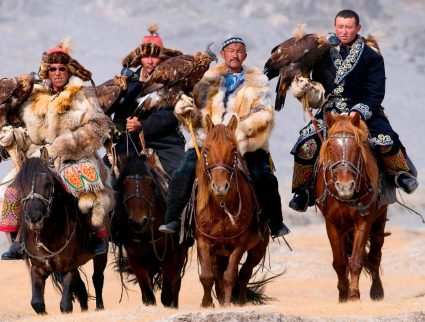 Eagle hunters riding horses to the Eagle Hunters festival in Mongolia.