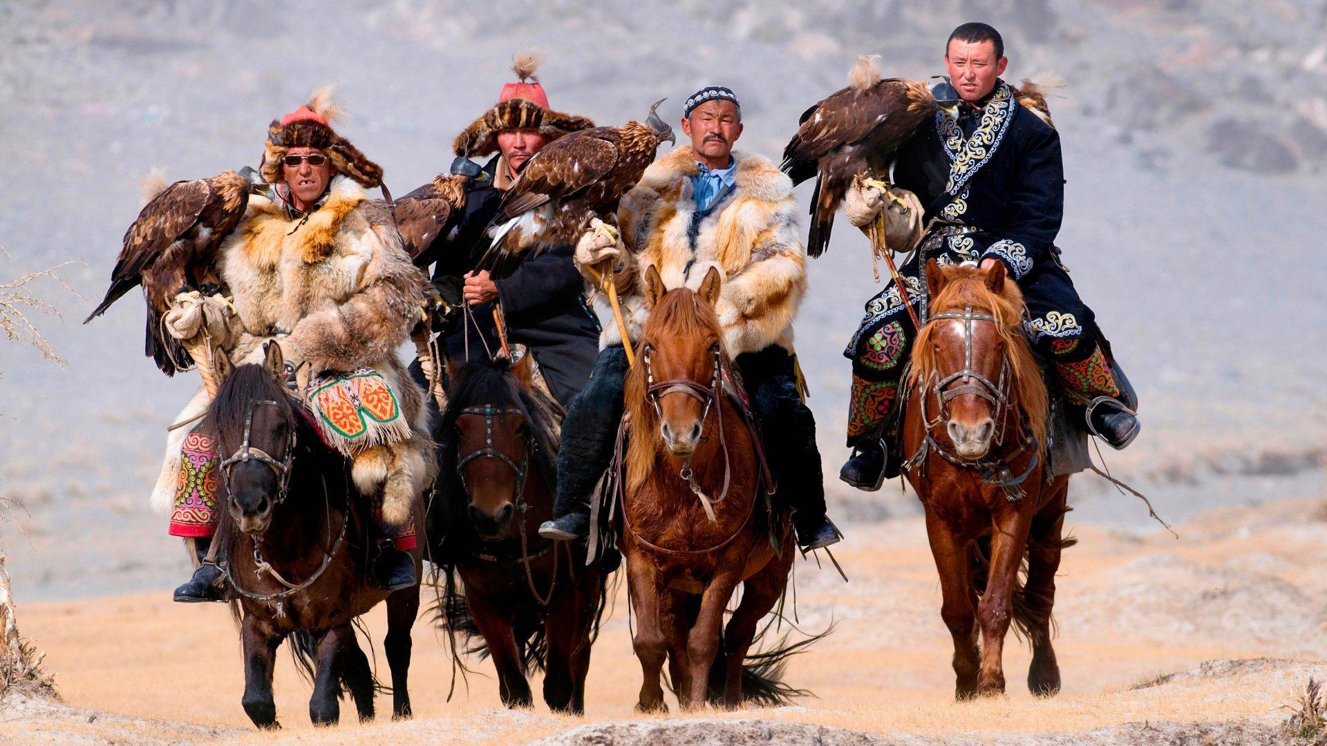 Eagle hunters riding horses to the Eagle Hunters festival in Mongolia.