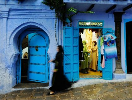 A woman walking down a street in the Chefchaouen medina, Morocco