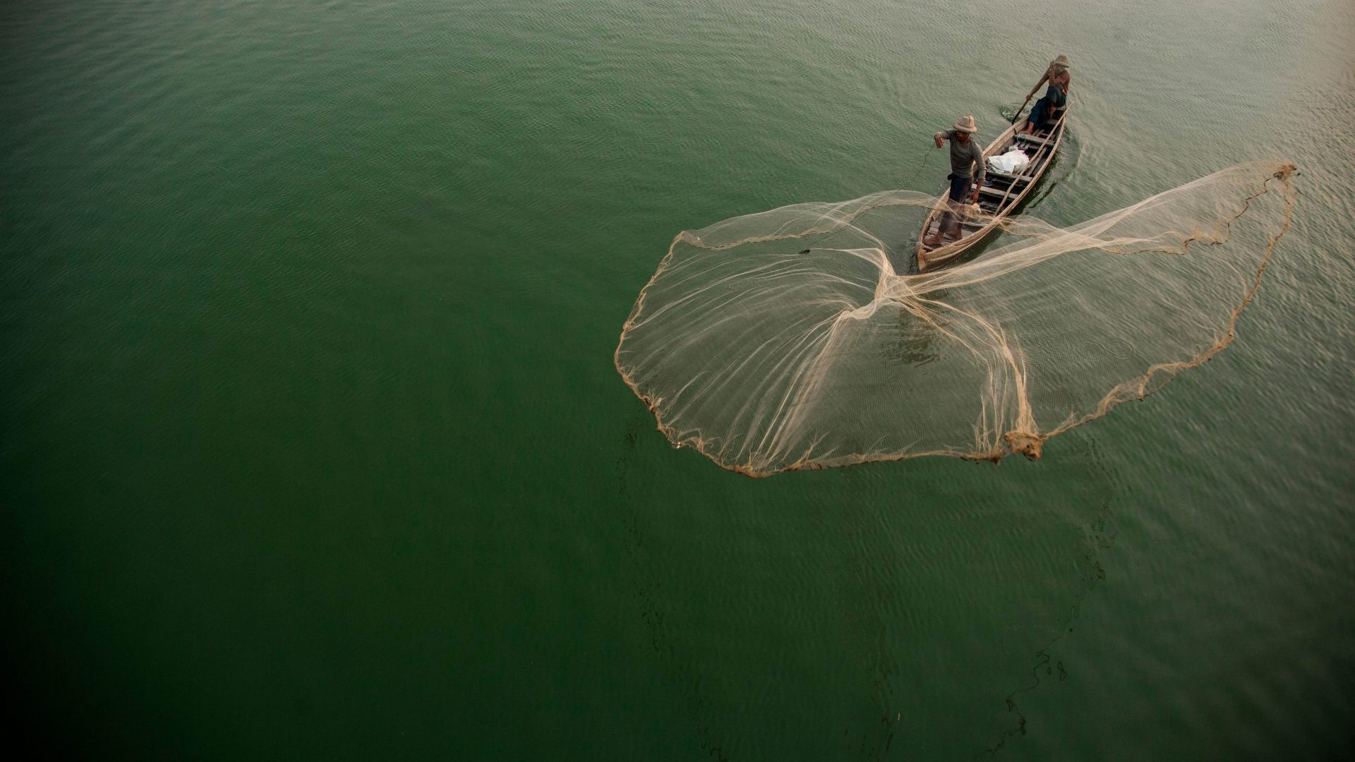 Fisherman casting net on Irrawaddy River, Mandalay, Myanmar with GeoEx