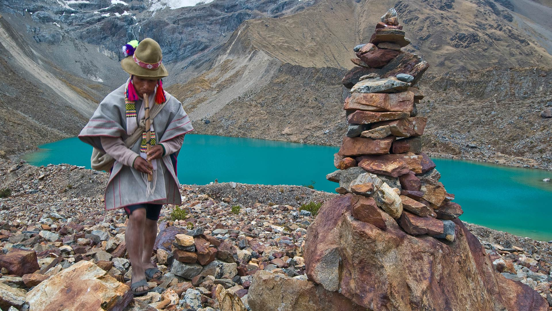 Peruvian man in front of glacial lake in Sacred Valley, Peru