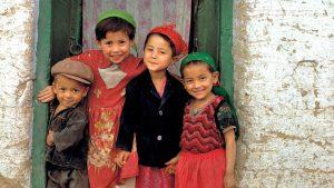 Friendly children smile from their doorway in Kashgar, China, Silk Road