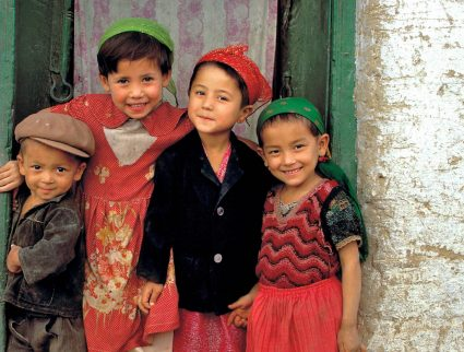 Friendly children smile from their doorway in Kashgar, China, Silk Road