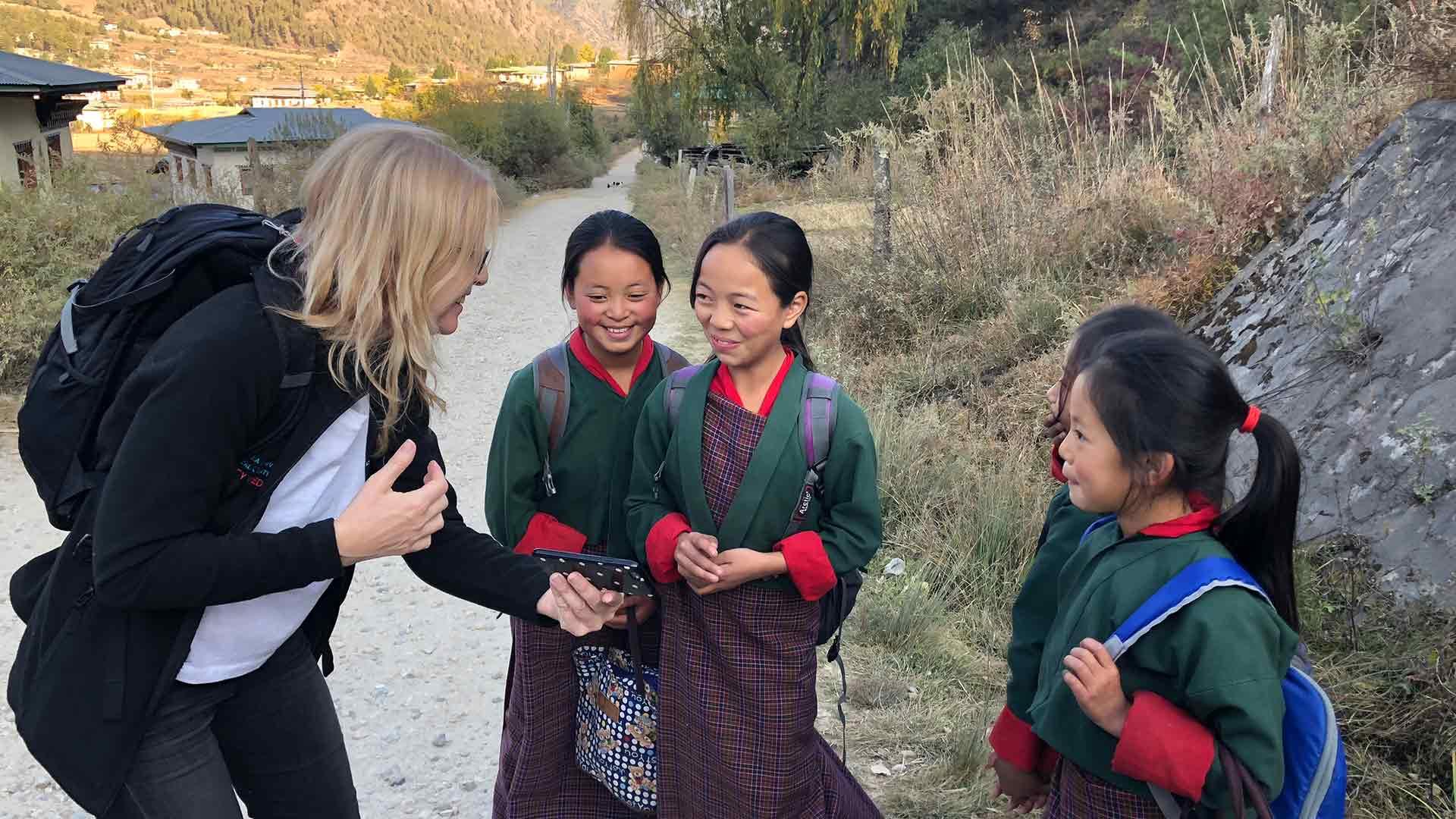 Bhutan traveler interacting with local schoolgirls