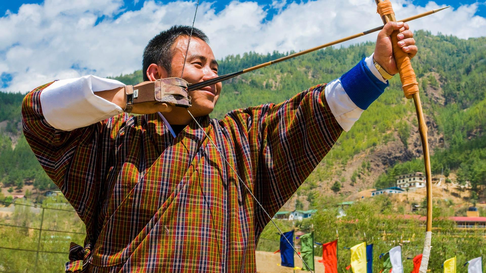 Bhutanese man in traditional dress practicing archery near Thimphu, Bhutan