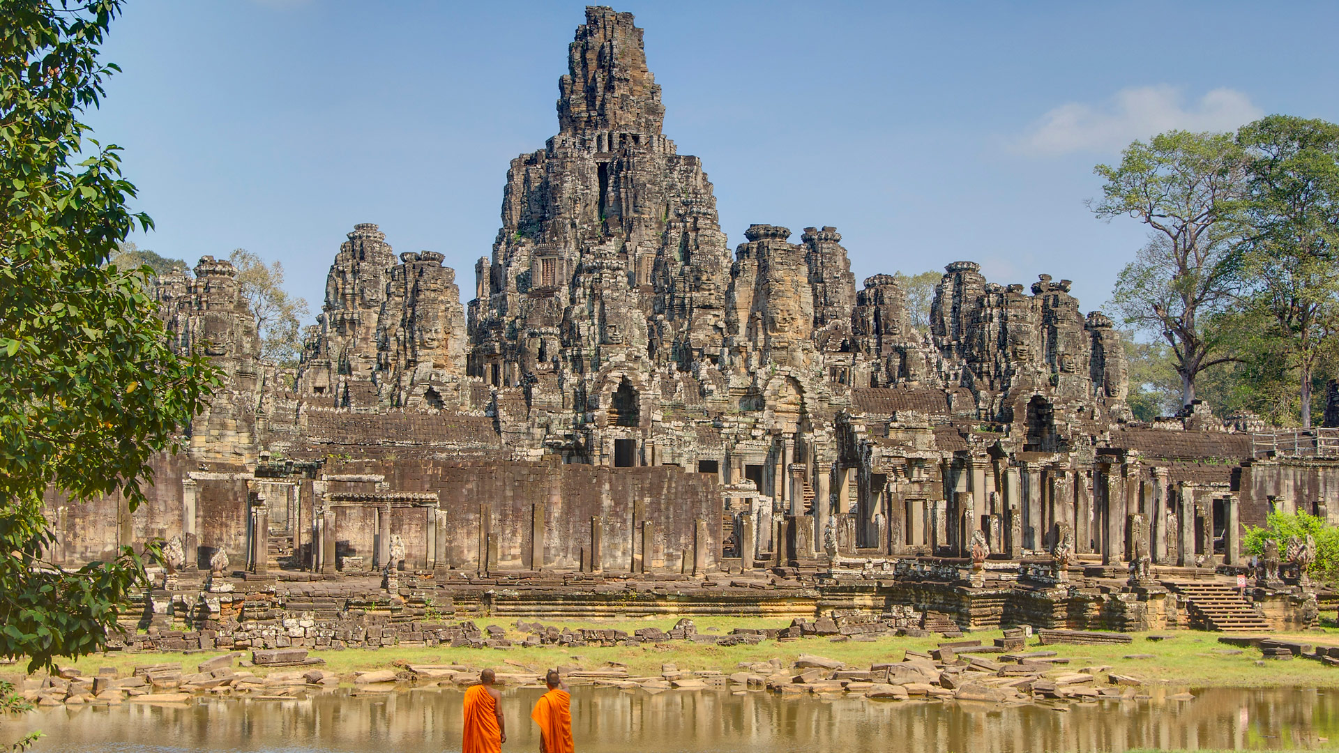 Monks looking at Bayon Temple, part of the Angkor UNESCO site, Cambodia with GeoEx