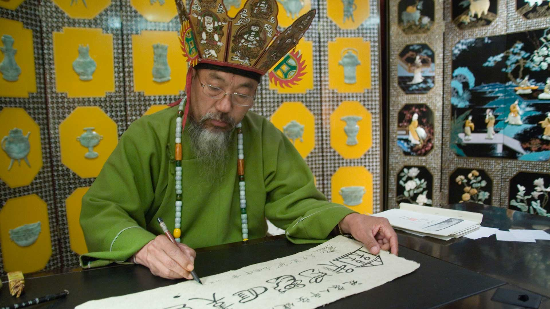 Classic Naxi calligrapher and pictogram scholar in Yunnan, China with GeoEx