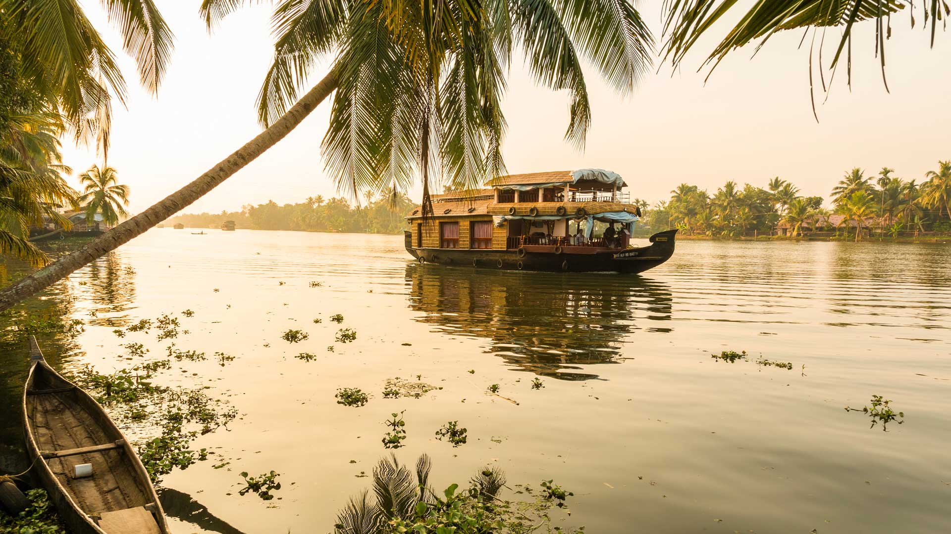 Traditional house boat navigating the Kerala backwaters near Alleppey, India with GeoEx