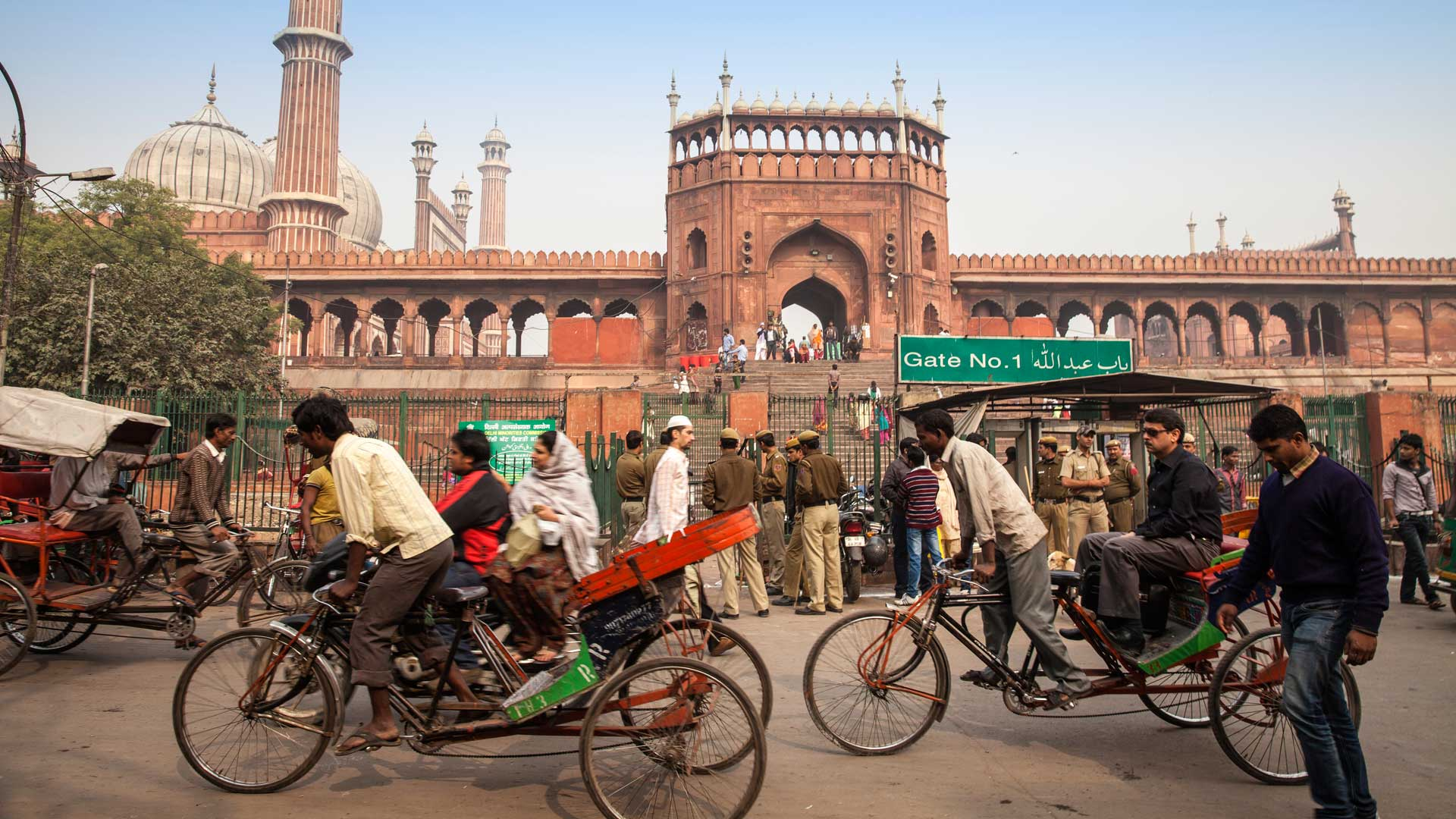 Rickshaws cycling past the Jama Masjid mosque in Old Delhi, India with GeoEx