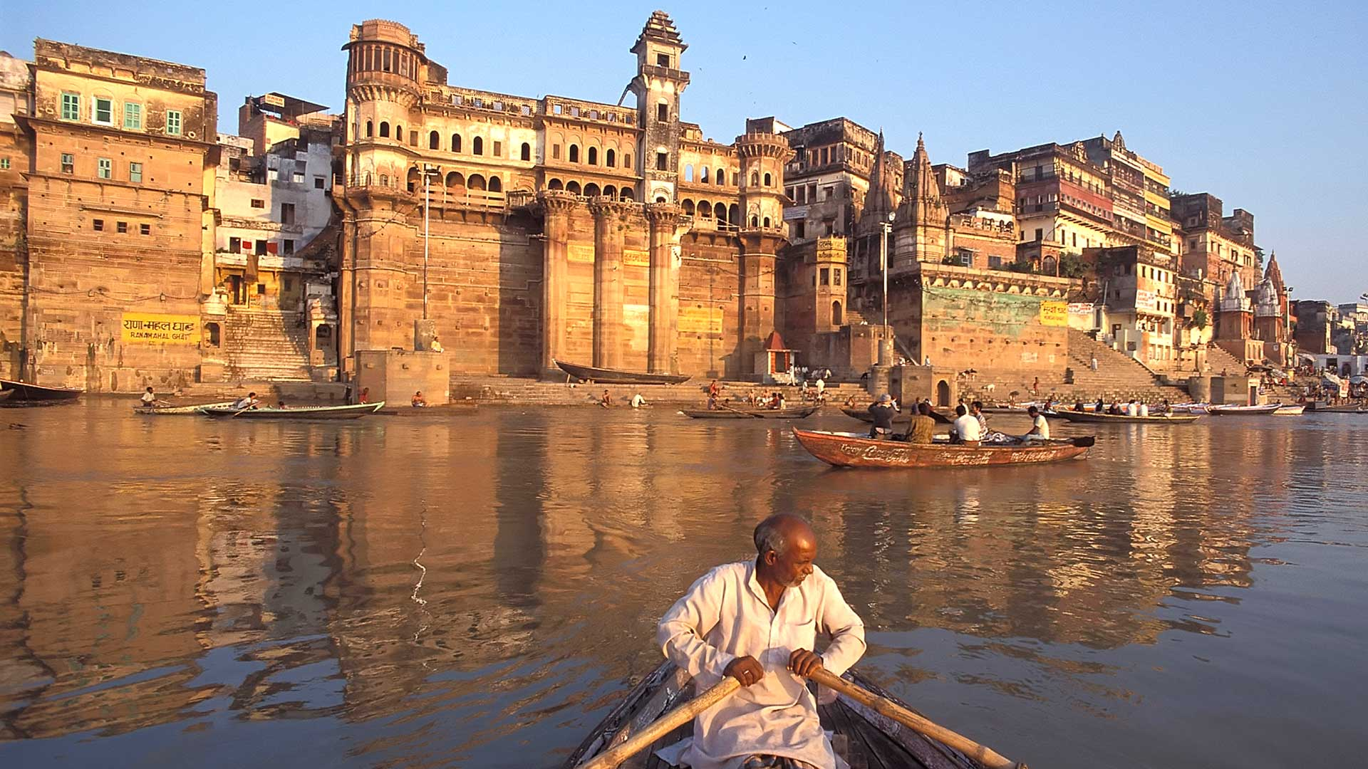 Man rowing a boat in front of the Bhij Rama Palace in Varanasi, India with GeoEx