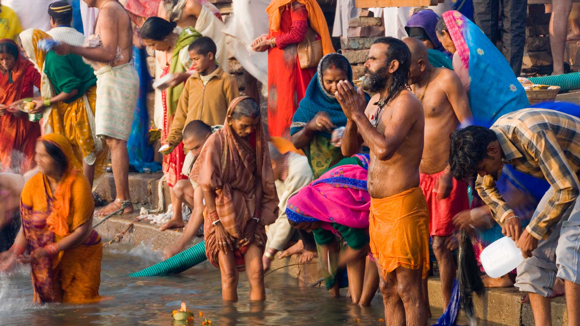 Pilgrims bathing in the holy Ganges River in Varanasi, India with GeoEx