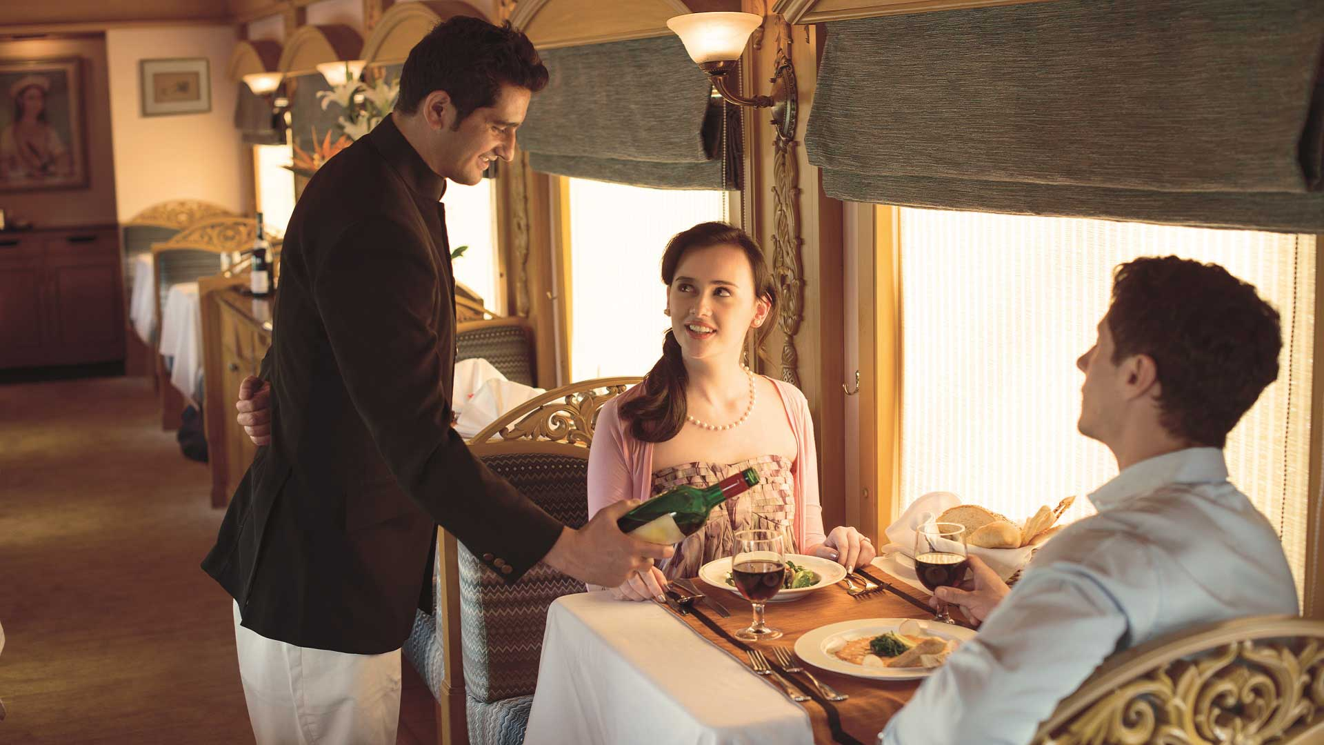A couple is served wine with their elegant meal aboard the Deccan Odyssey train en route across India with GeoEx