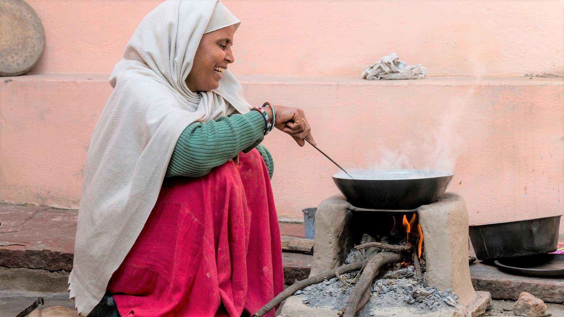 Woman joyfully cooking in Fatehpur Sikri village of Rajasthan, India with GeoEx