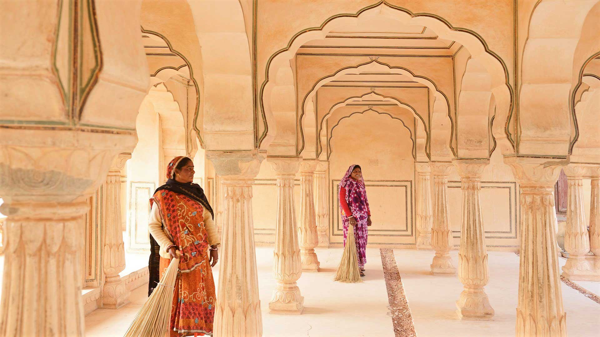 Two sari-clad women stand under elegant archways of Amer (Amber) Fort in Jaipur, India with GeoEx