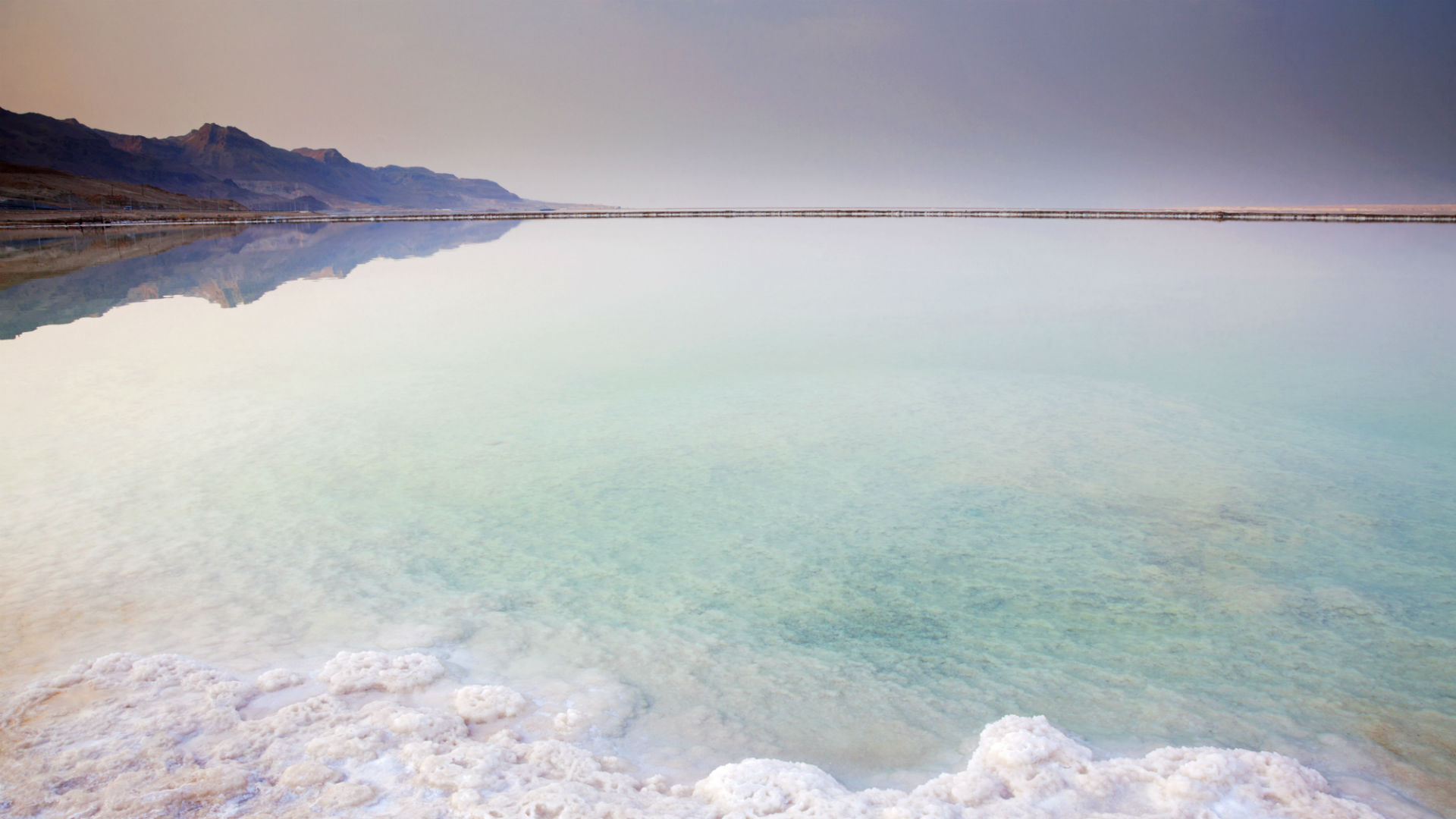The Southern part of the dead sea in Israel with salt formations on the shore and colors due to its mineral and salt formations.