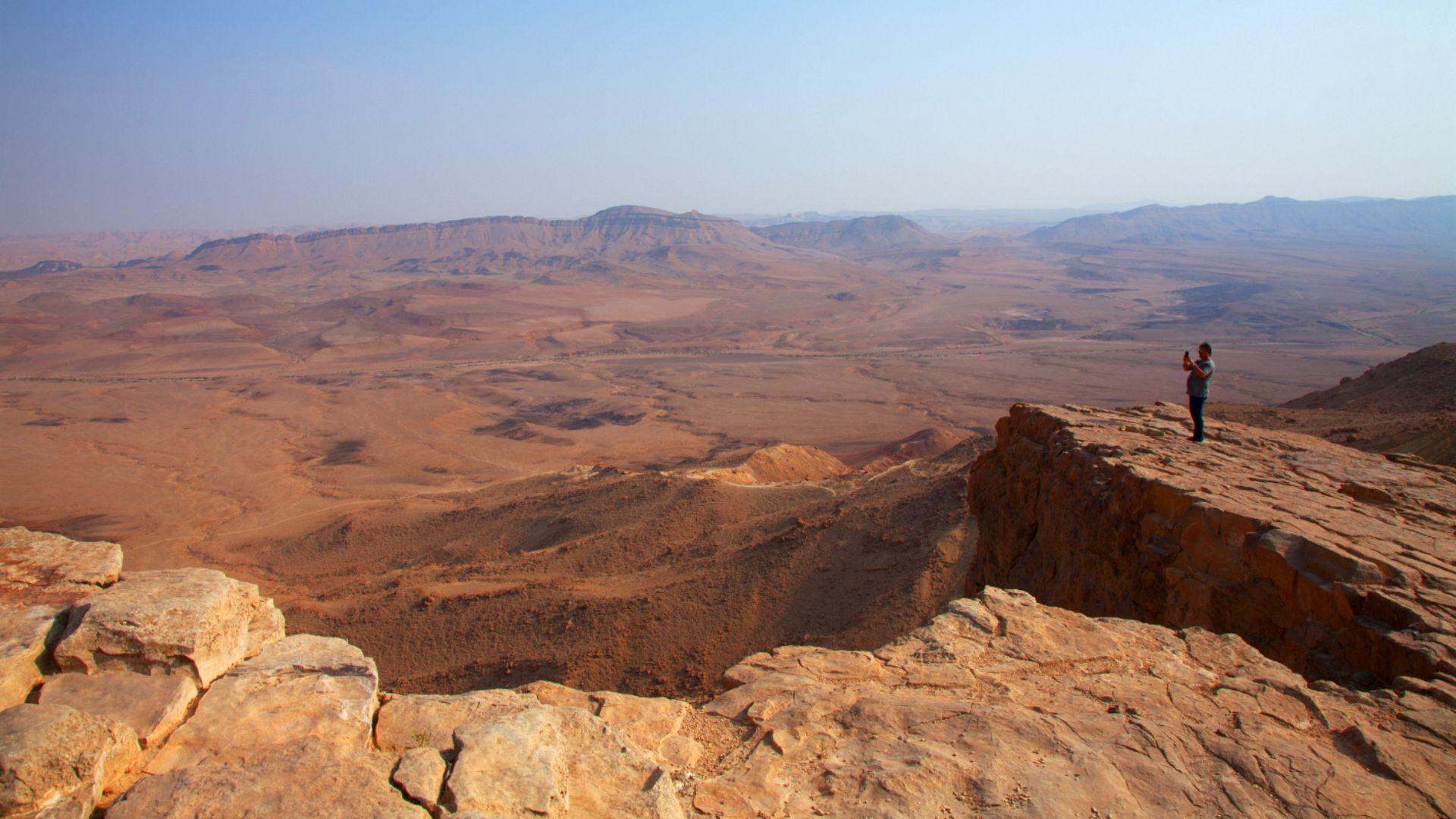 Man overlooking Negev desert crater of Mitzpe, Ramon in Israel.