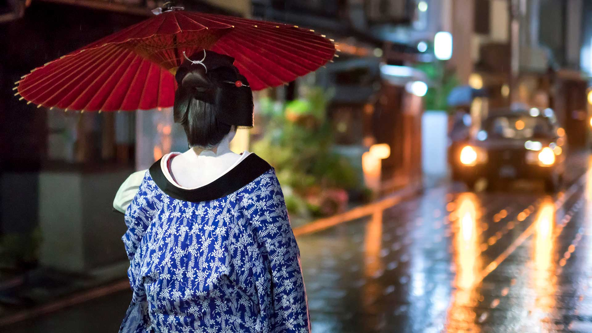 Maiko with umbrella walking along a street, Gion district, Kyoto, Japan