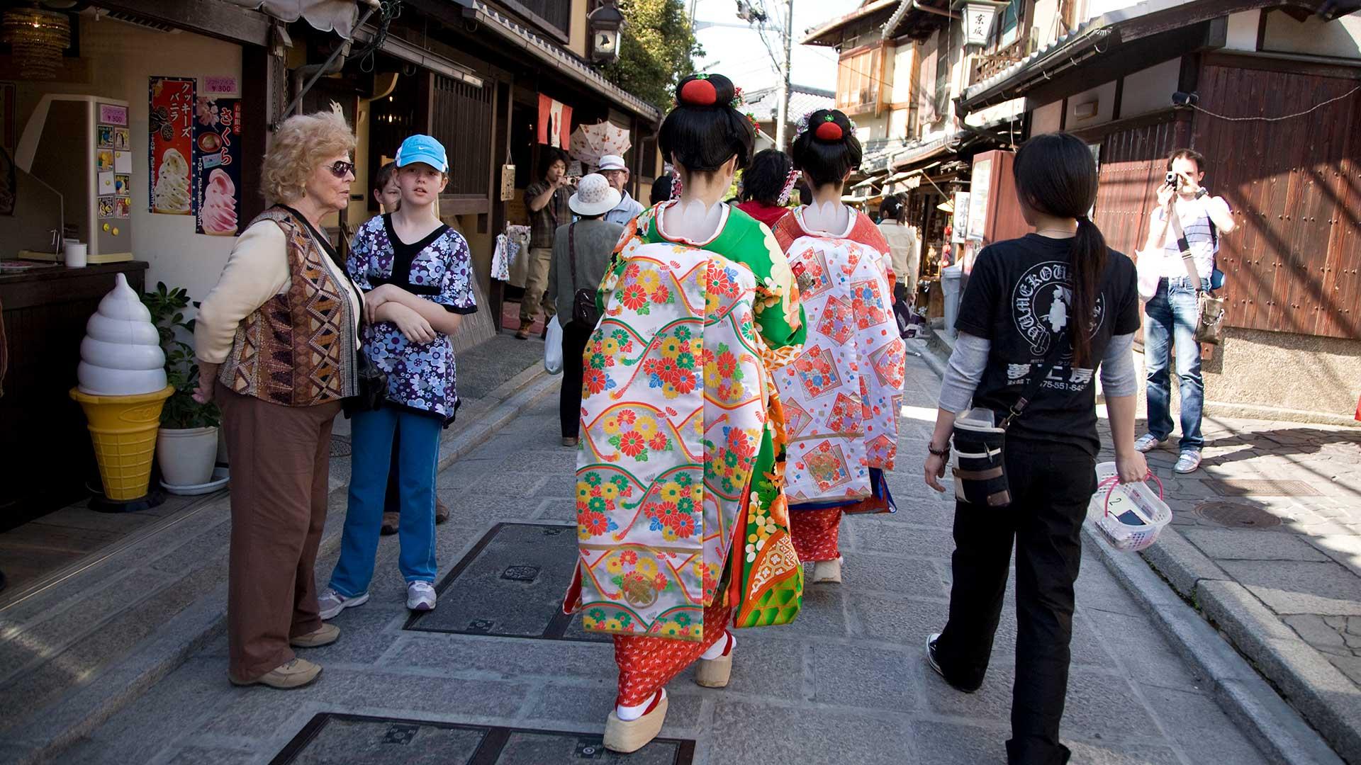 Kyoto, Gion district, tourists watch Geisha in kimonos walk by