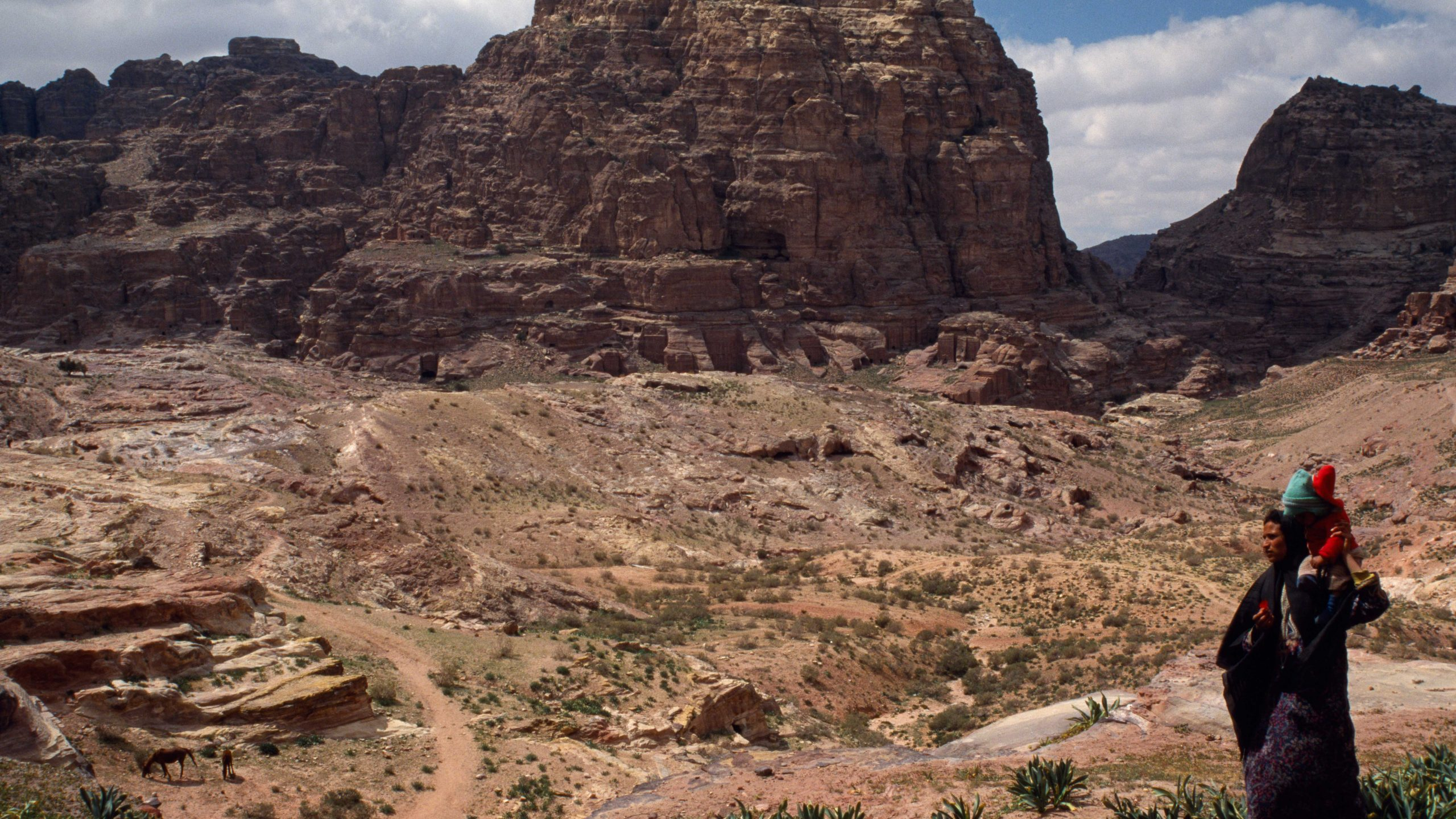 A Bedouin carries a child home amidst the spectacular landscapes of ancient Petra, Jordan.