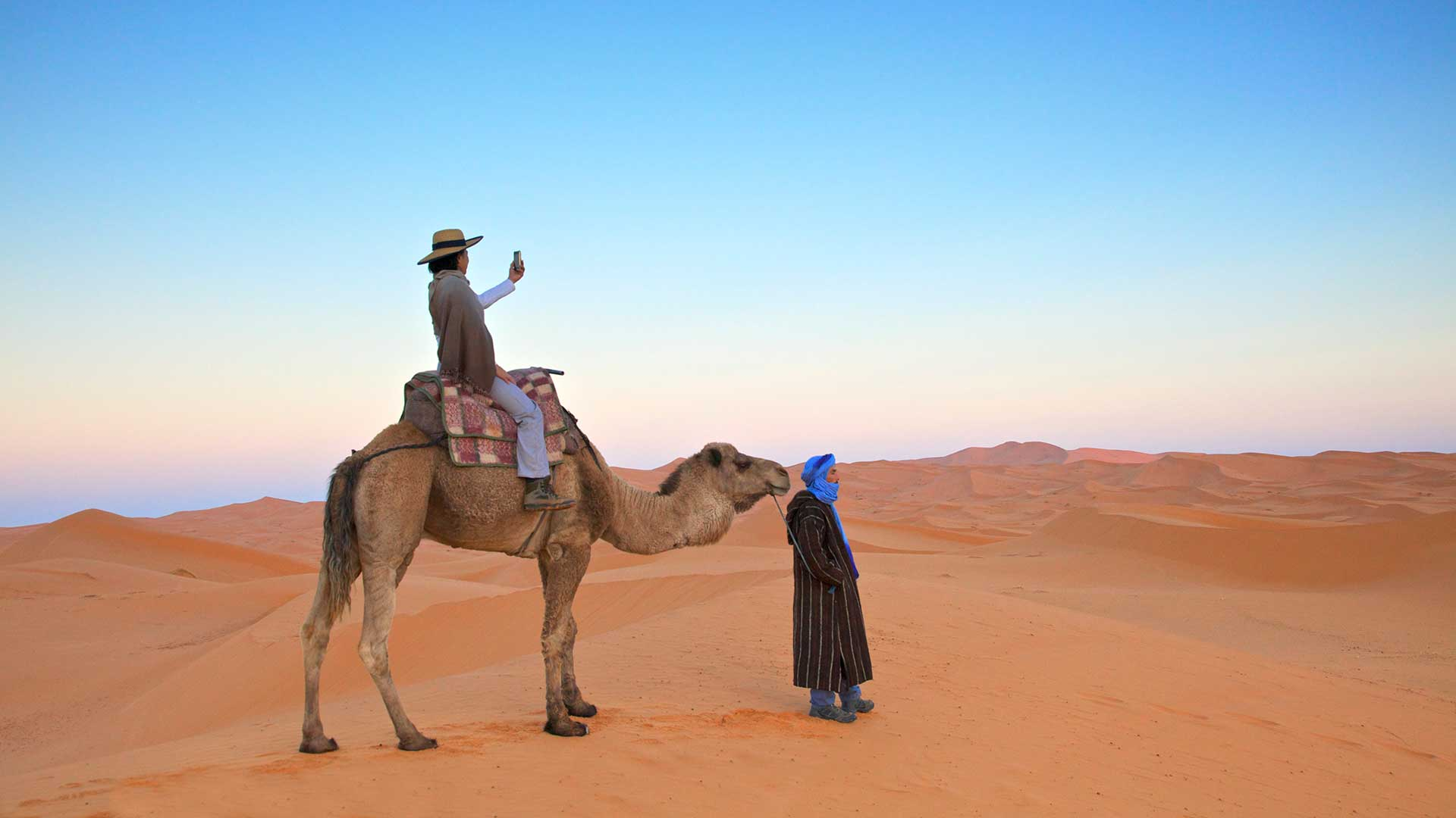 In the desert on a camel taking a photograph, Merzouga