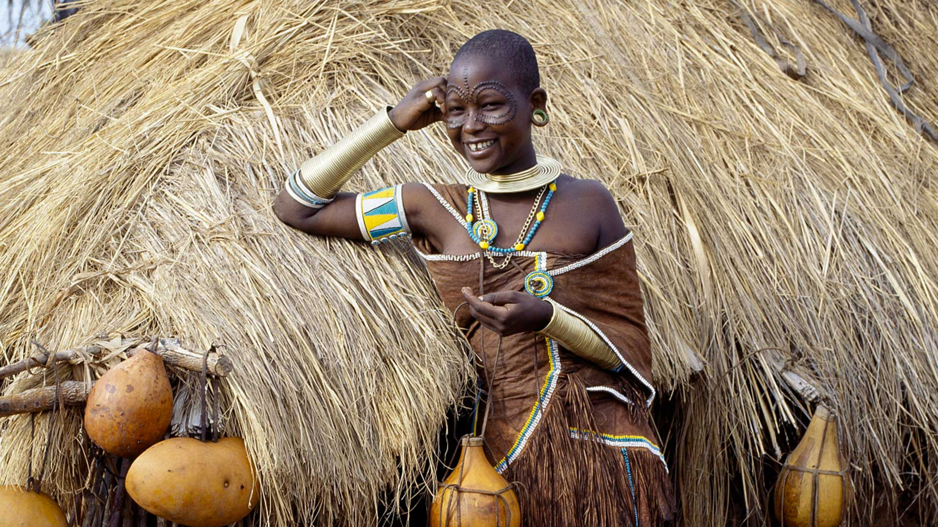 A Datoga woman relaxes outside her thatched house, Tanzania.