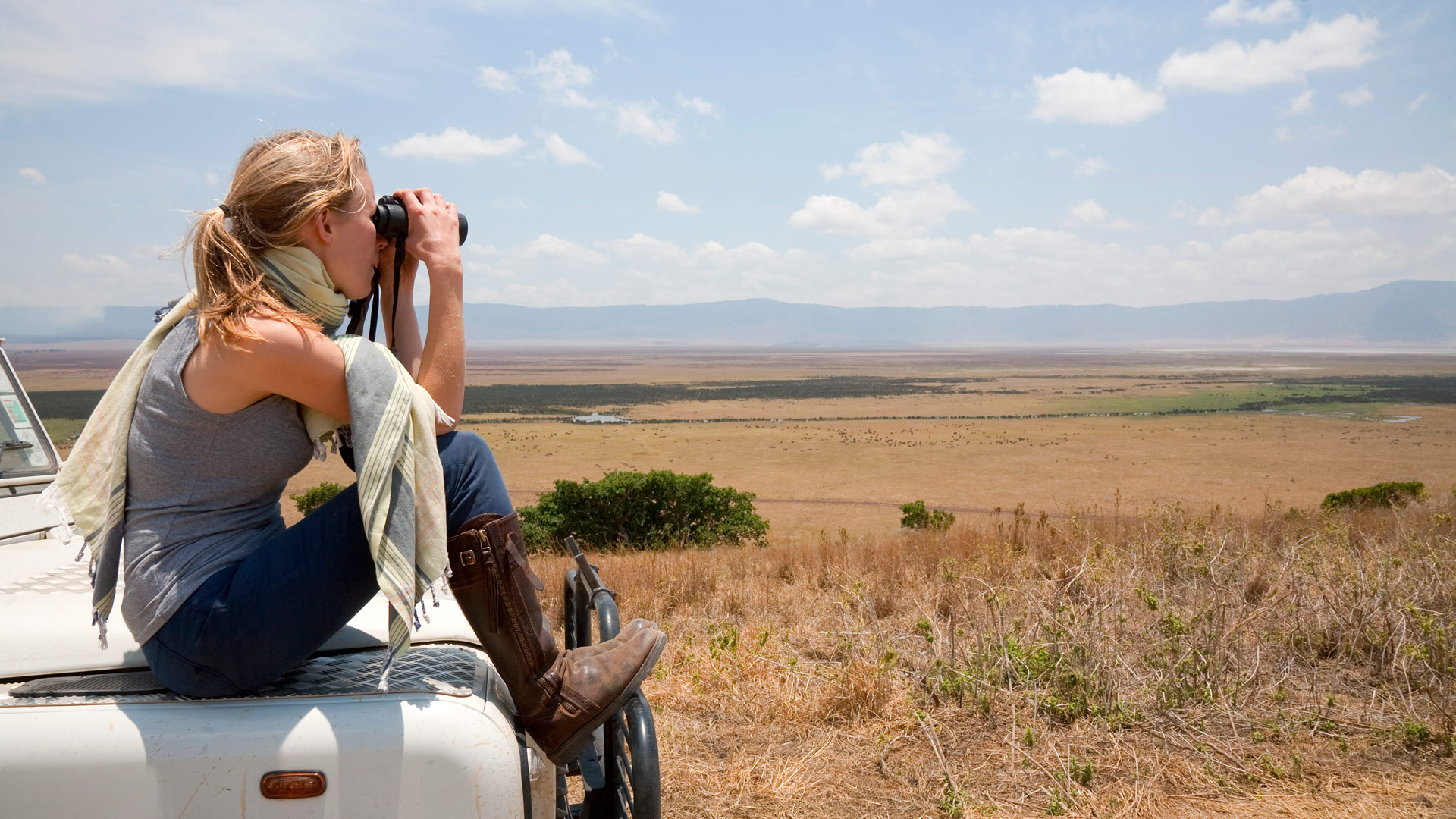 A woman on safari looking for wildlife in Tanzania from the hood of a Land Rover.