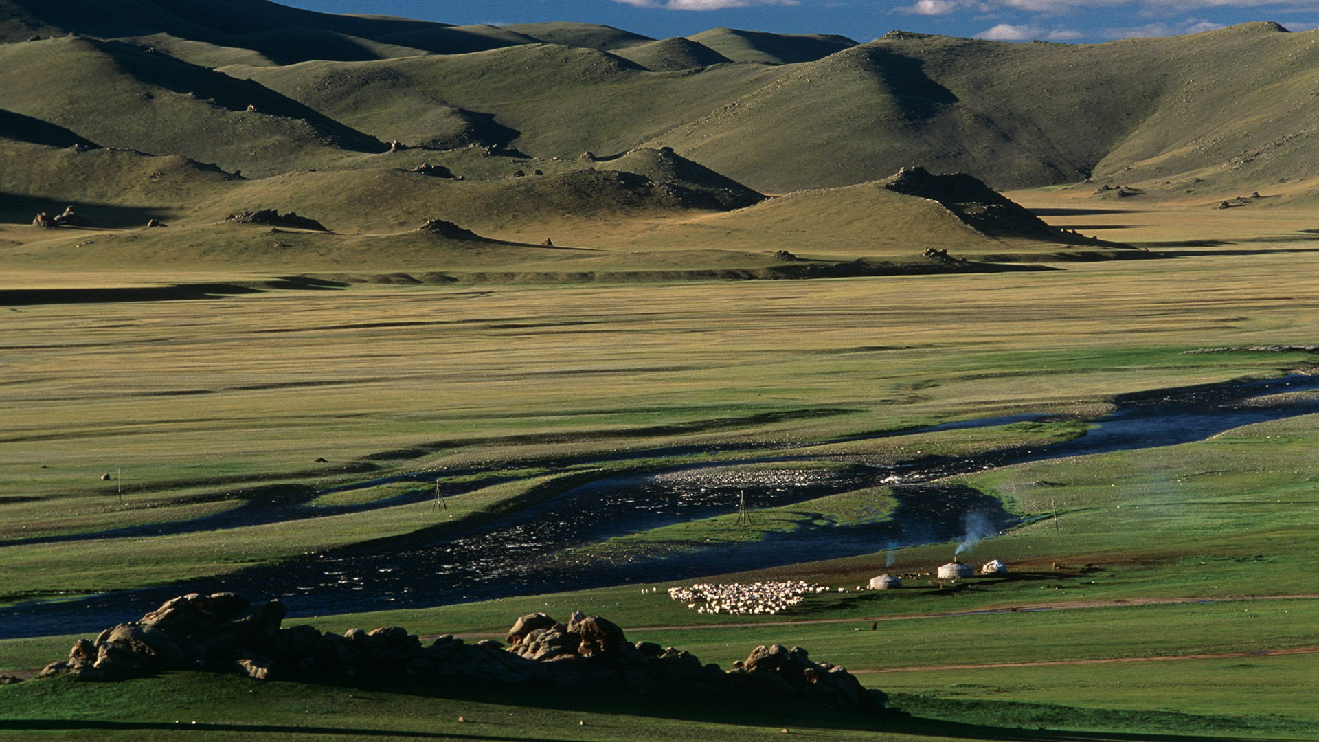 Yurts next to a river on the steppeland, Mongolia with GeoEx