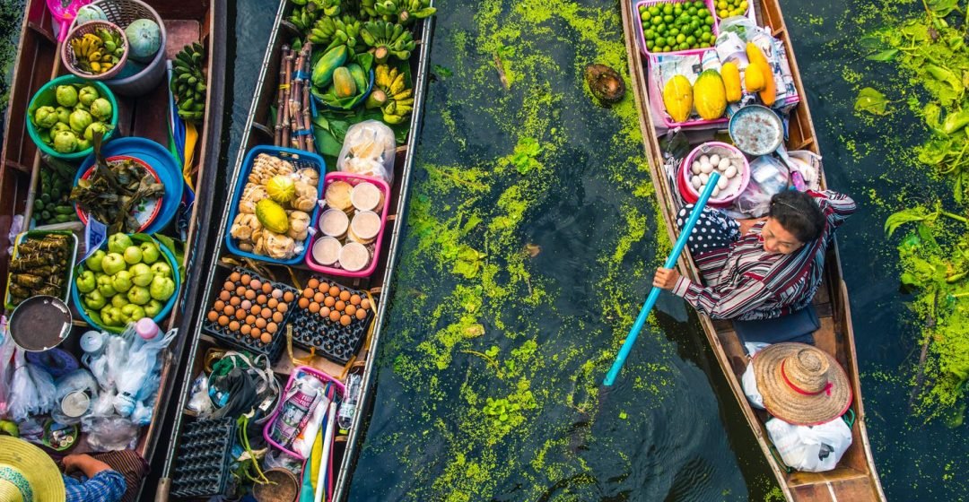 Female vendor sells food from a longtail boat at a floating market in Bangkok, Thailand