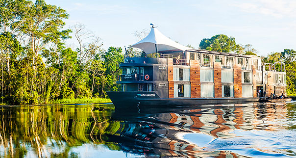 The Aqua Expeditions Aria riverboat navigates a waterway in the Amazon, Peru