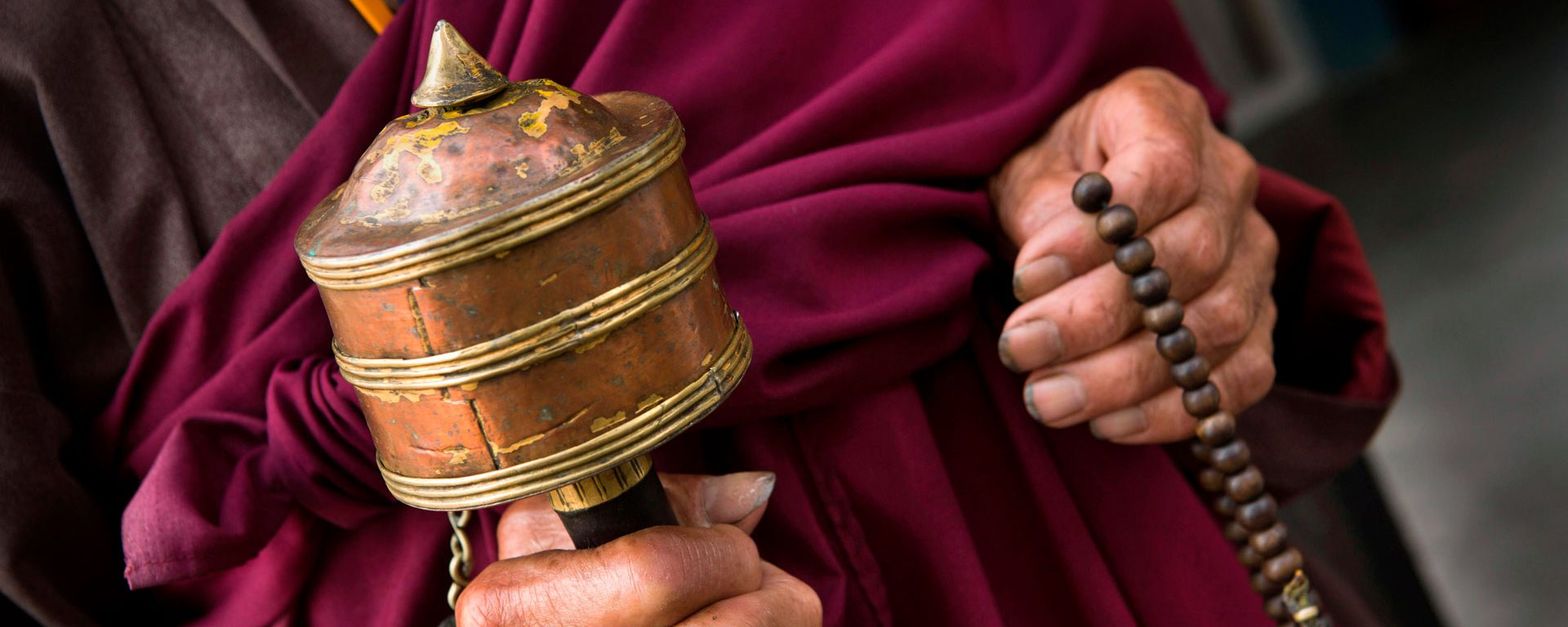 Hands of old monk holding prayer wheel and beads, Rangjung Monastery, Trashigang, Eastern Bhutan