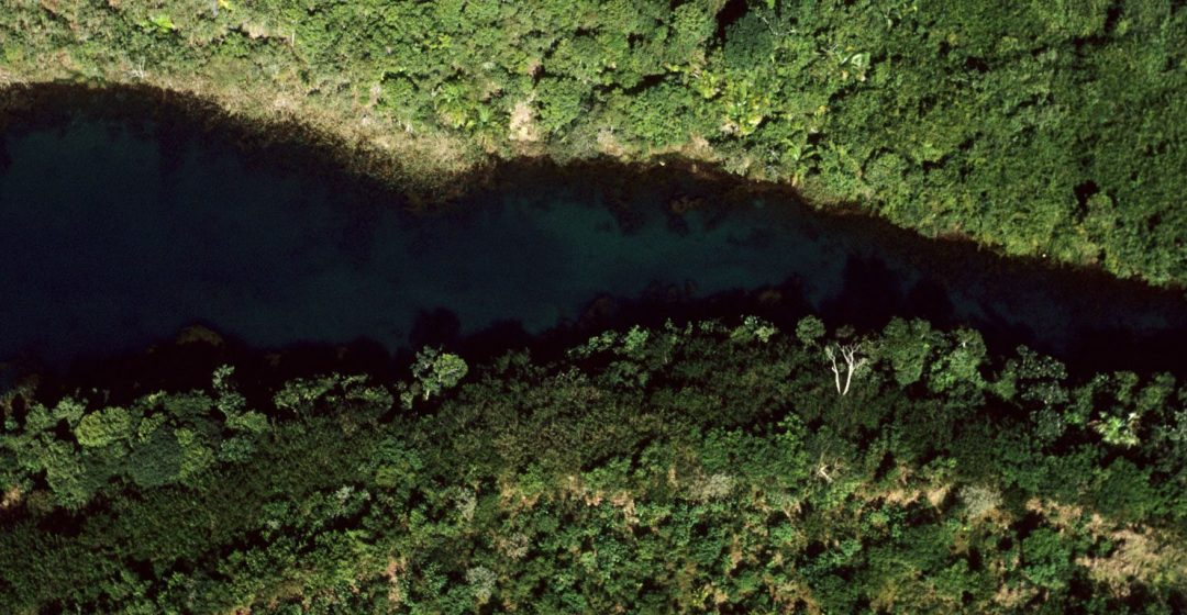 Aerial view of a deep blue river flowing through the rain forest in the Amazon, Brazil