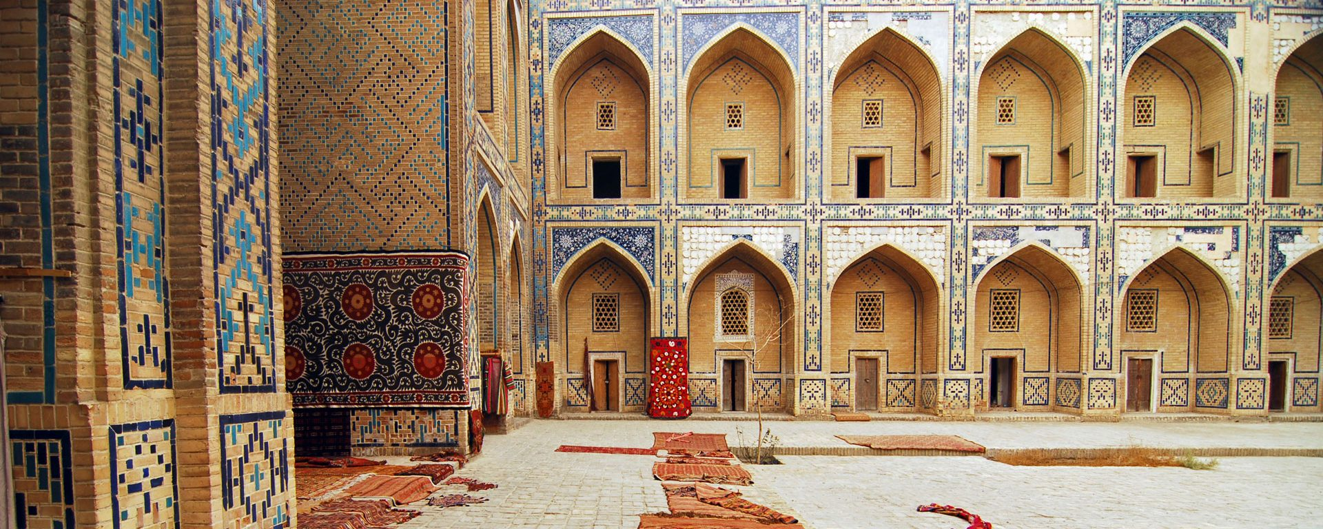Uzbekistan, Bukhara, arched entrance in a row of historic buildings with carpets lying on courtyard.