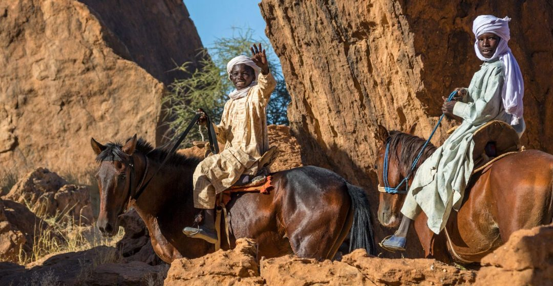 Tubu boys ride horses among large boulders in the Ennedi Desert, Chad
