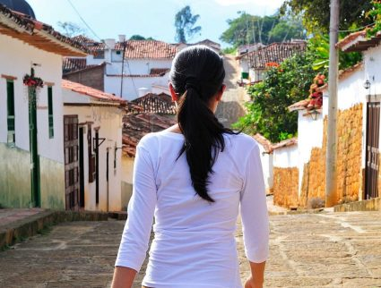 Woman walking down a street in the colonial town of Barichara, Colombia, South America.